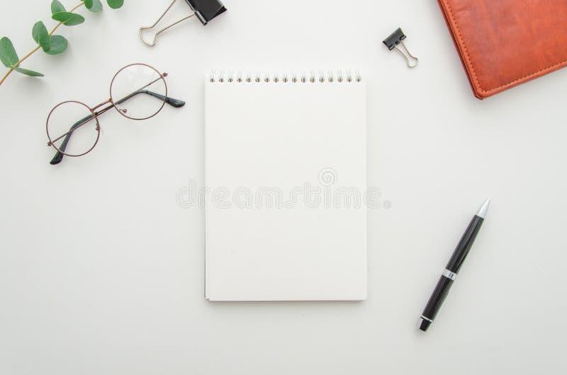 Vista superior de la mesa blanca de la oficina con la libreta espiral en blanco, los vidrios, las fuentes y la cartera de cuero M fotografía de archivo