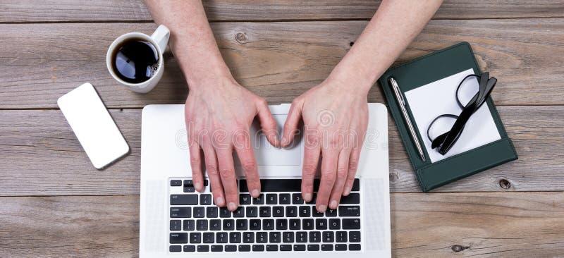Vista superior de la mesa de trabajo con las manos en el teclado del ordenador portátil con o imagen de archivo