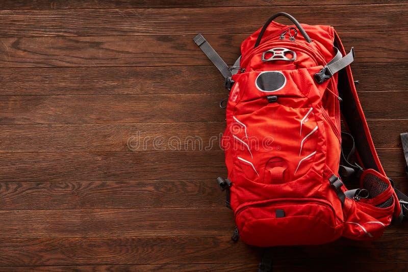 Vista superior de la mochila anaranjada brillante del viaje en un fondo de madera imagen de archivo libre de regalías