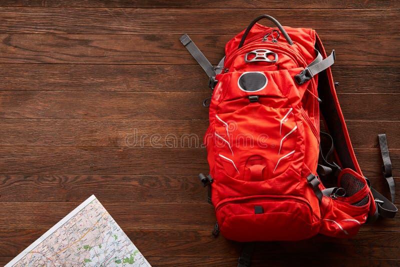 Vista superior de la mochila anaranjada del viaje con el mapa en el fondo de madera fotografía de archivo