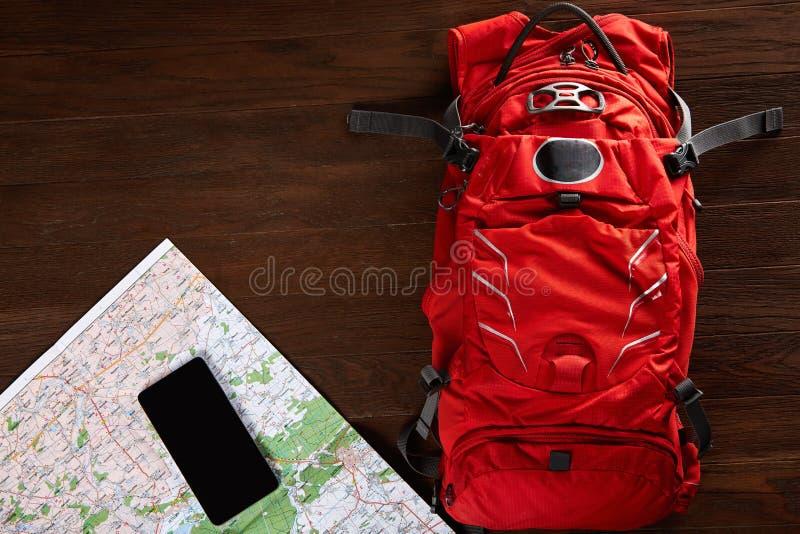 Vista superior de la mochila del viaje con el mapa y del teléfono en el fondo de madera foto de archivo