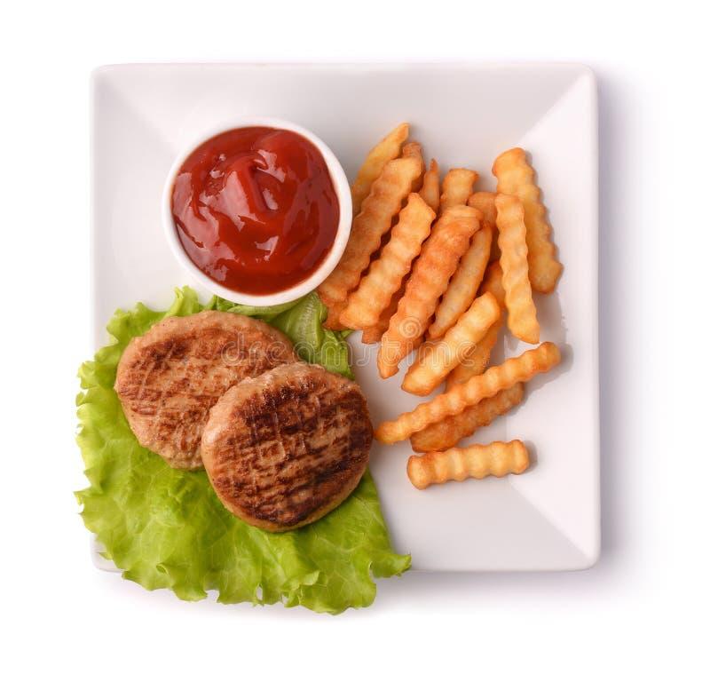 Vista superior de la placa con las hamburguesas, las fritadas y la salsa de tomate fotografía de archivo libre de regalías