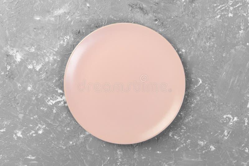 Vista superior de la placa rosada vacía de la ronda mate en el espacio oscuro del fondo del cemento para usted diseño imagenes de archivo