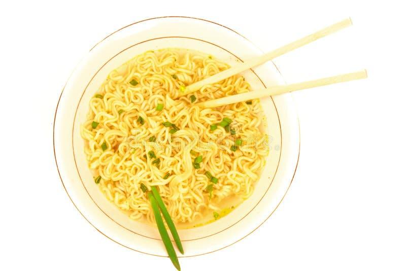 Vista superior de la placa de la sopa de la comida rápida con la cebolla verde, los palillos y los tallarines inmediatos de los r imagen de archivo