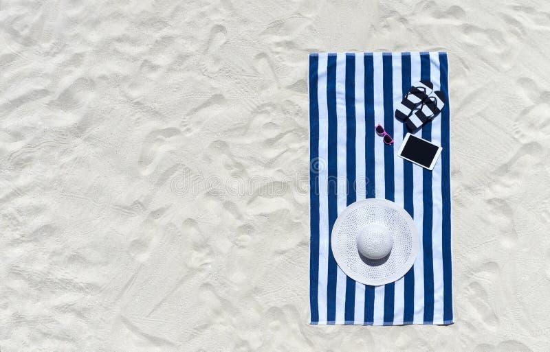 Vista superior de la playa arenosa con los accesorios del marco y del verano de la toalla imagenes de archivo