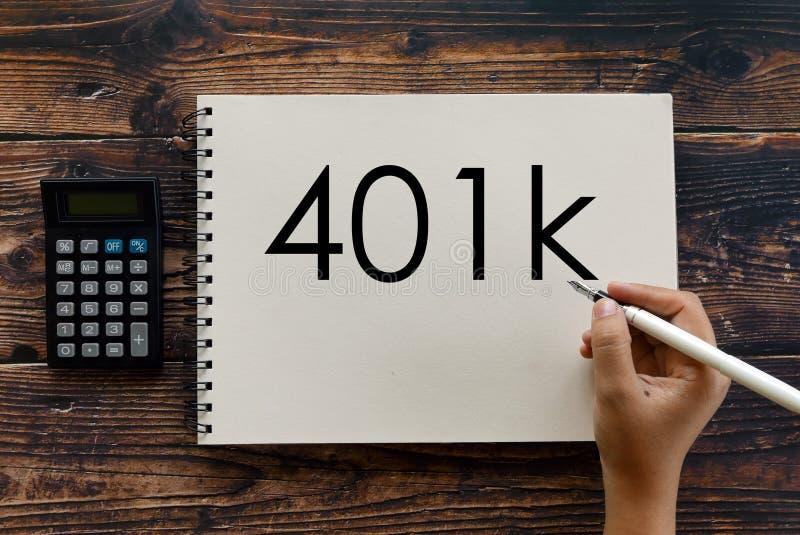 Vista superior de la pluma de tenencia de la calculadora, del cuaderno y de la mano que escribe 401k imagen de archivo libre de regalías