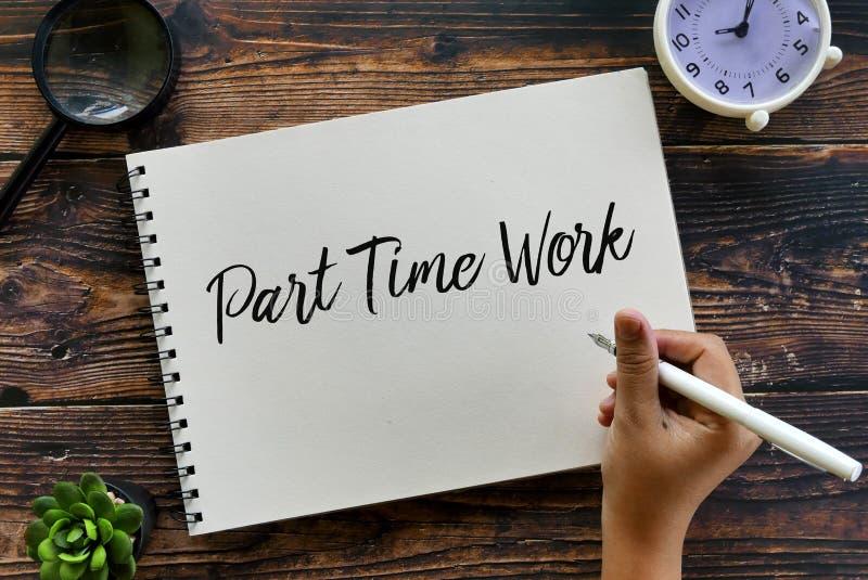 Vista superior de la pluma de tenencia de la lupa, de la planta, del reloj y de la mano que escribe el trabajo a tiempo parcial e foto de archivo libre de regalías
