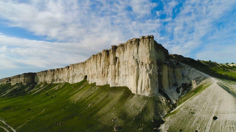Vista superior de la roca blanca hermosa con la hierba verde en fondo del cielo azul tiro Panorama del acantilado blanco con verd foto de archivo libre de regalías
