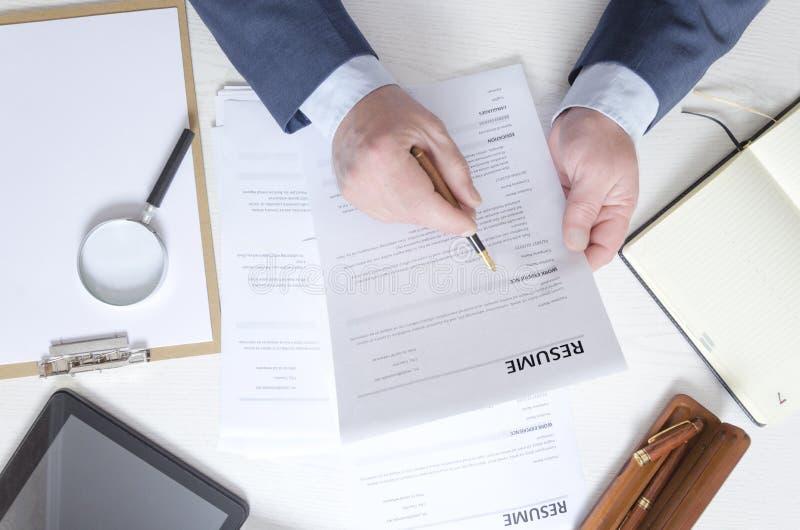Vista superior de la tabla del reclutador que trabaja con el curriculum vitae y que elige al gran empleado imagen de archivo