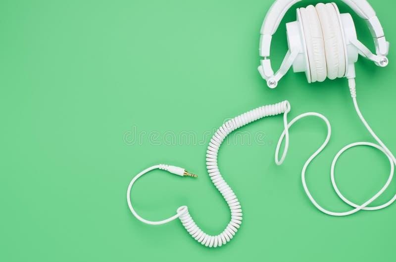 Vista superior de la tabla de un ni?o adolescente, auriculares de la composici?n en fondo verde claro foto de archivo libre de regalías