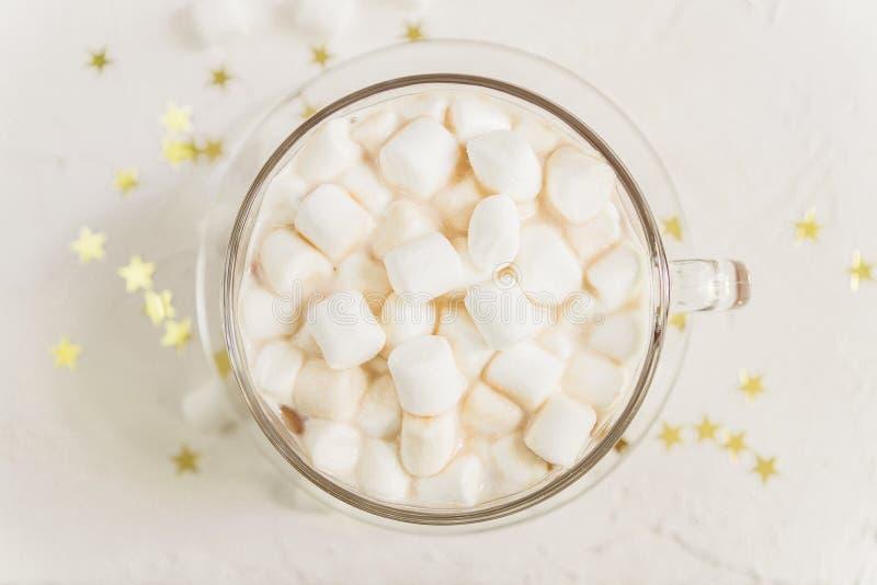 Vista superior de la taza de bebida deliciosa caliente del cacao con las melcochas en fondo de las estrellas del oro fotografía de archivo