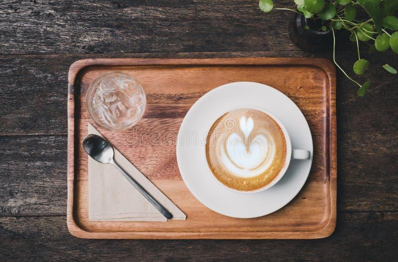 Vista superior de la taza de café caliente con la agua fría y la cuchara en el tra de madera imágenes de archivo libres de regalías