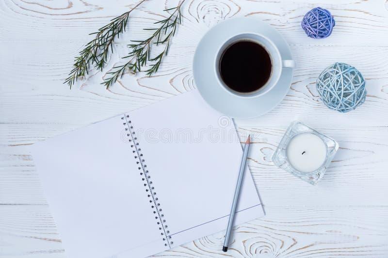 Vista superior de la taza de café, de la libreta en blanco, del lápiz, de flores y de velas en la tabla blanca fotos de archivo
