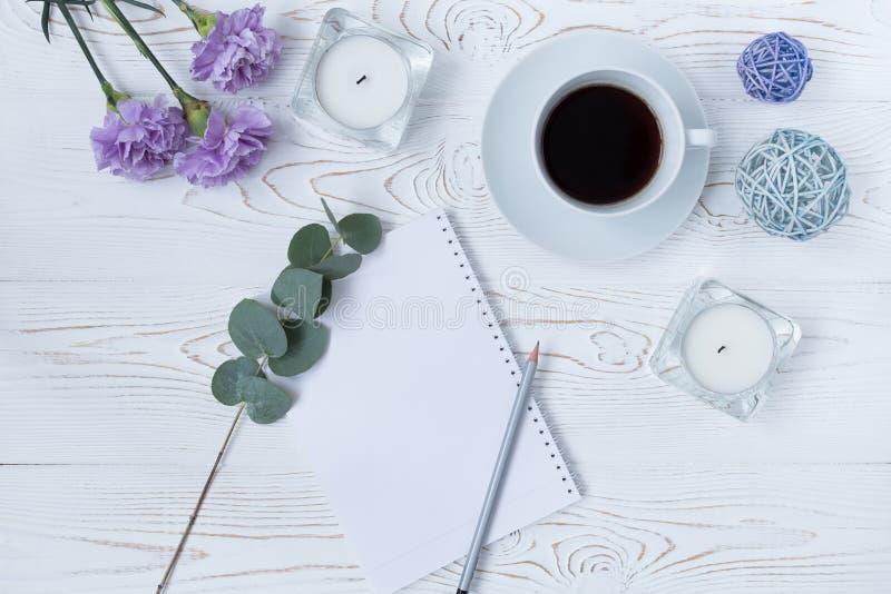 Vista superior de la taza de café, de la libreta en blanco, del lápiz, de flores y de velas en la tabla blanca Endecha plana foto de archivo libre de regalías