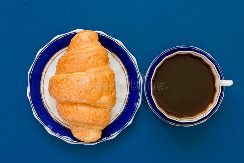 Vista superior de la taza de coffe negro y del cruasán en una placa en fondo azul Desayuno de la mañana en estilo francés imágenes de archivo libres de regalías