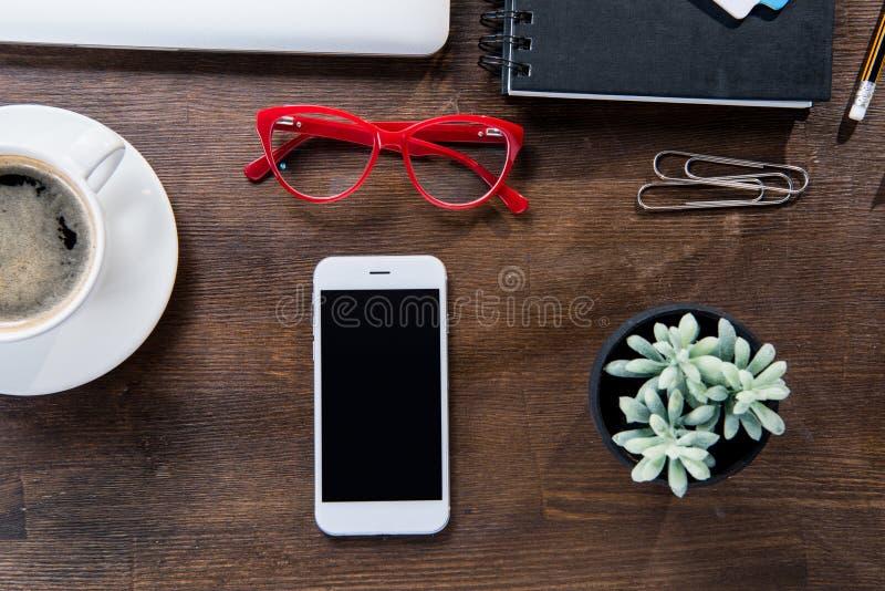 Vista superior de la taza de café, smartphone con la pantalla en blanco, cuaderno, lentes rojas y planta suculenta en pote imagenes de archivo