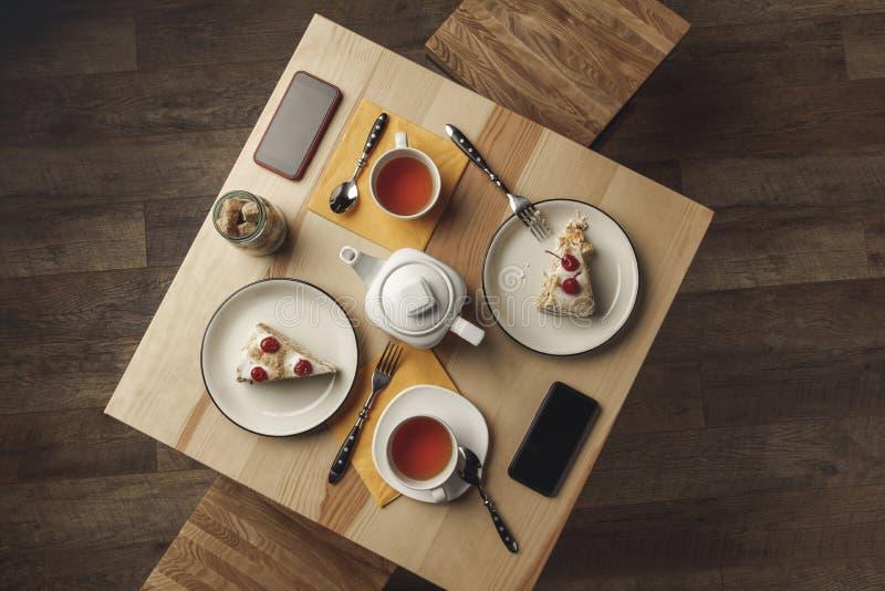 vista superior de la tetera, de tazas de té, de pasteles y de smartphones con las pantallas en blanco imágenes de archivo libres de regalías