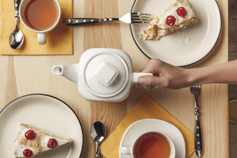 vista superior de la tetera de la tenencia de la persona y juego de té con los pasteles fotos de archivo