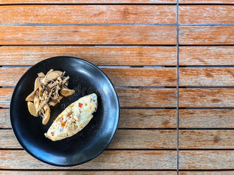 Vista superior de la tortilla sana de la clara de huevo con la seta del orinji en una placa negra y una tabla de madera imágenes de archivo libres de regalías