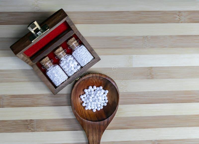 Vista superior de las botellas de cristal de píldoras homeopáticas en un retro diseñado en la viejos caja de madera y glóbulos en imagen de archivo
