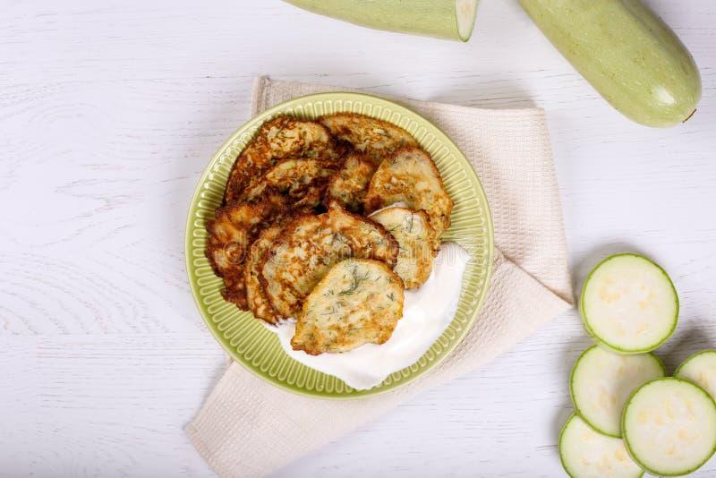 Vista superior de las crepes vegetarianas del calabacín en el fondo de madera blanco foto de archivo