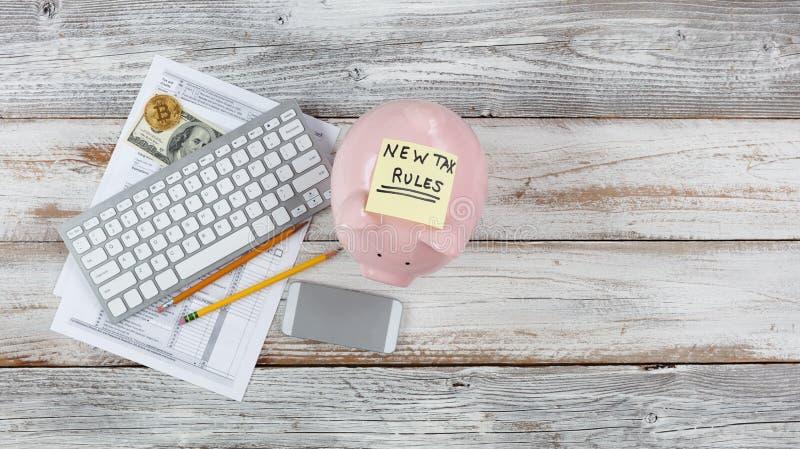 Vista superior de las formas del impuesto sobre la renta con los nuevos cambios más la hucha en el escritorio rústico blanco fotografía de archivo libre de regalías