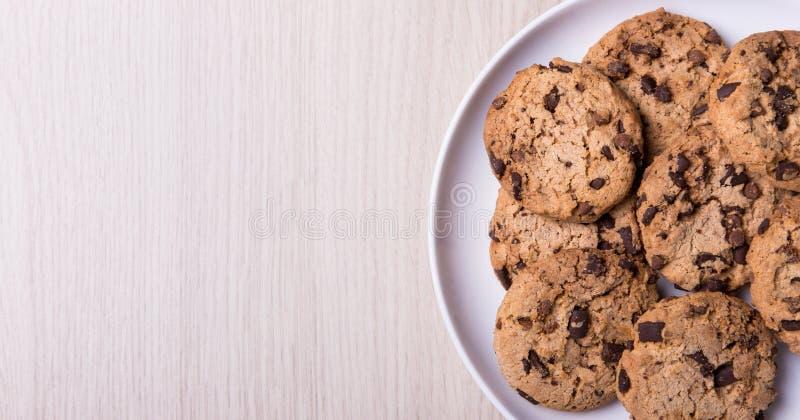 Vista superior de las galletas del chocolate en el espacio blanco de la placa y de la copia en w fotos de archivo libres de regalías