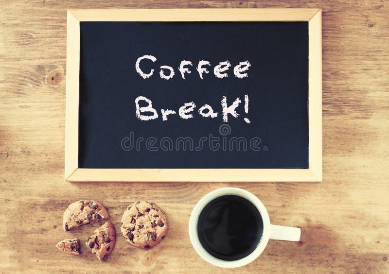 Vista superior de las galletas y de la pizarra de la taza de café con el descanso para tomar café de la frase escrito en él imagen de archivo libre de regalías