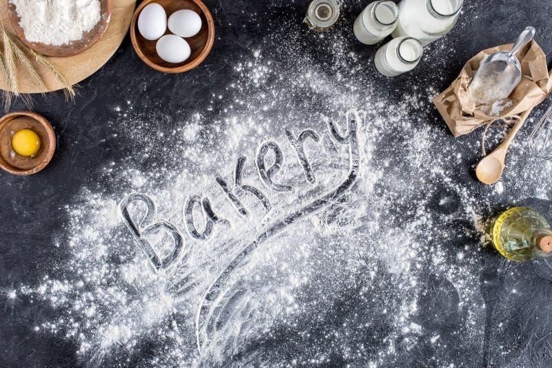 Vista superior de las letras de la panadería hecha de la harina y de los diversos ingredientes para cocer foto de archivo