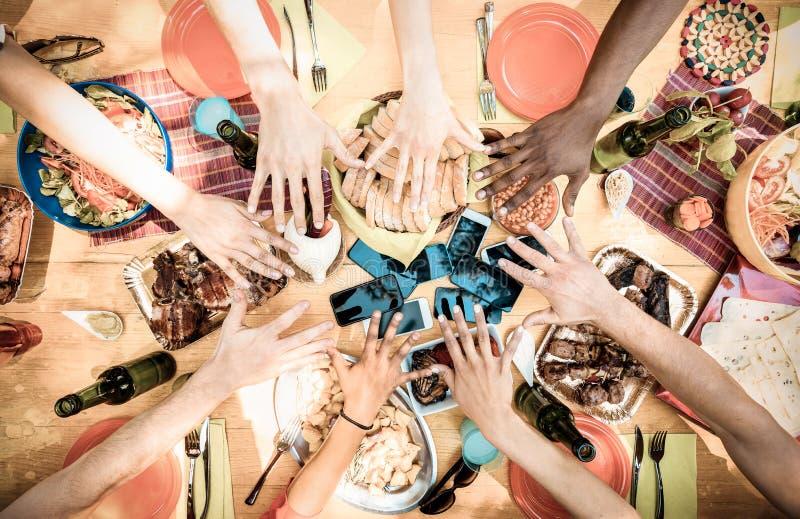 Vista superior de las manos del amigo en la comida con los teléfonos elegantes móviles fotos de archivo libres de regalías