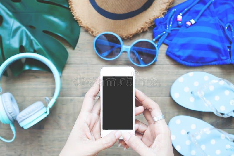 Vista superior de las manos del ` s de la mujer usando smartphone con los artículos del verano encendido fotografía de archivo