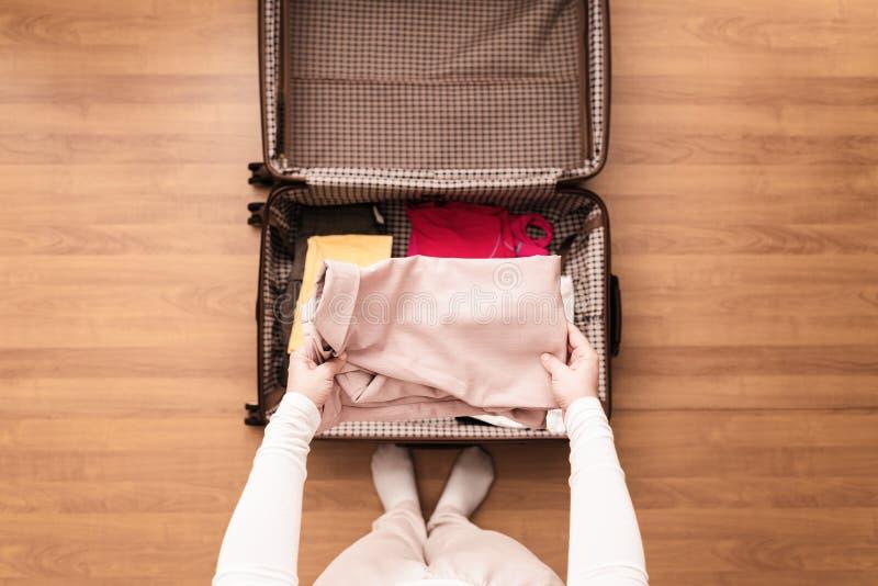 Vista superior de las manos de la mujer que embalan una chaqueta rosada en una maleta del equipaje para un nuevo viaje foto de archivo