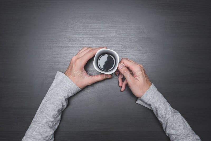 Vista superior de las manos masculinas que sostienen una taza de café en fondo de madera negro de la tabla foto de archivo