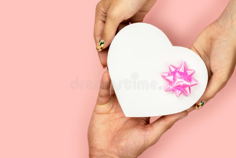 Vista superior de las manos masculinas y femeninas que sostienen la caja de regalo del corazón de la forma con el arco rosado en  fotografía de archivo