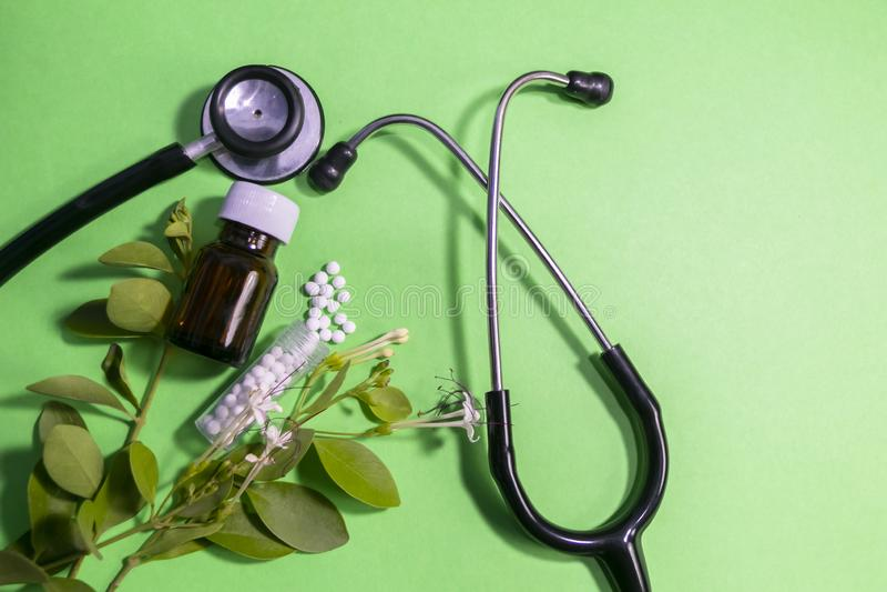 Vista superior de las píldoras homeopáticas del glóbulo y de la botella de cristal líquida con los estetoscopios y las hojas en f imágenes de archivo libres de regalías