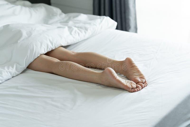 Vista superior de las piernas delgadas de una mujer Piernas desnudas de una mujer joven que duerme en su foco suave de la cama en imagen de archivo libre de regalías