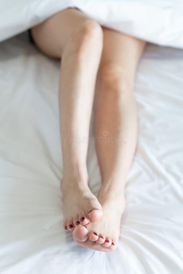 Vista superior de las piernas delgadas de una mujer Piernas desnudas de una mujer joven que duerme en su foco suave de la cama en fotos de archivo libres de regalías
