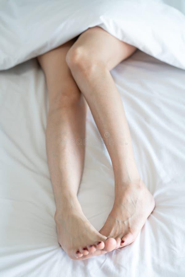 Vista superior de las piernas delgadas de una mujer Piernas desnudas de una mujer joven que duerme en su foco suave de la cama en foto de archivo