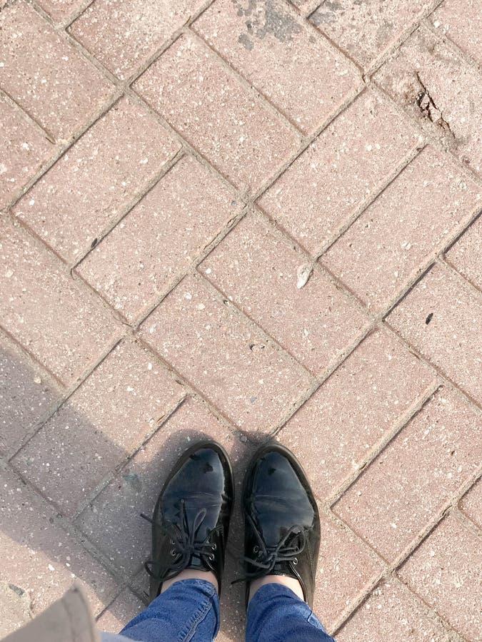 Vista superior de las piernas, zapatos, pies de las muchachas, mujeres en charol foto de archivo