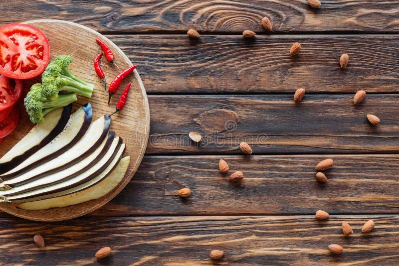 vista superior de las pimientas cortadas frescas de la berenjena, de los tomates, del bróculi y de chile en tabla de cortar en el fotos de archivo