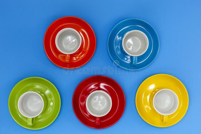 Vista superior de las tazas de café coloridas en fondo azul fotos de archivo
