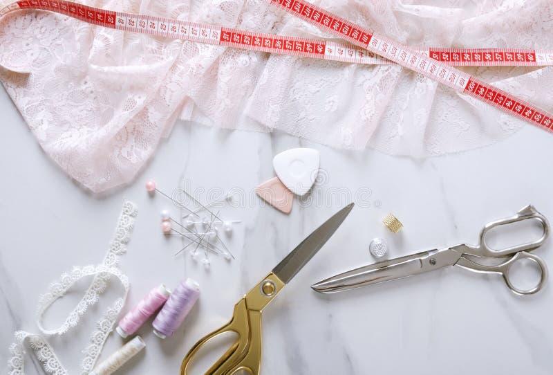 Vista superior de las tijeras rosadas del cordón, de la cinta métrica, de oro y de plata, pernos de costura en la tabla de mármol foto de archivo