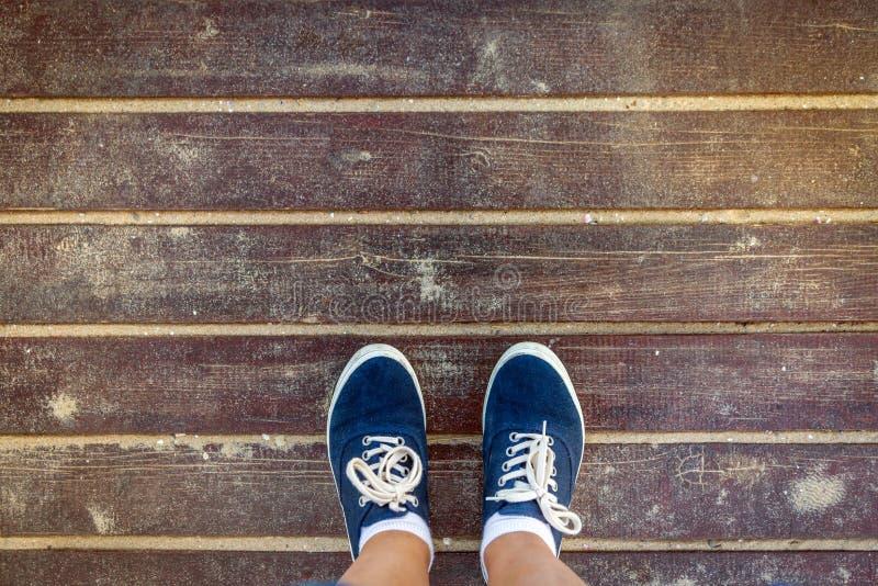 Vista superior de las zapatillas de deporte azules que se colocan en piso de madera viejo fotos de archivo