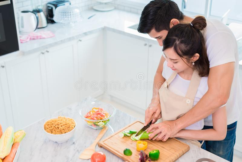Vista superior de los amantes o de los pares asiáticos que cocinan el desayuno por la mañana en sitio de la cocina Mujer de enseñ fotos de archivo