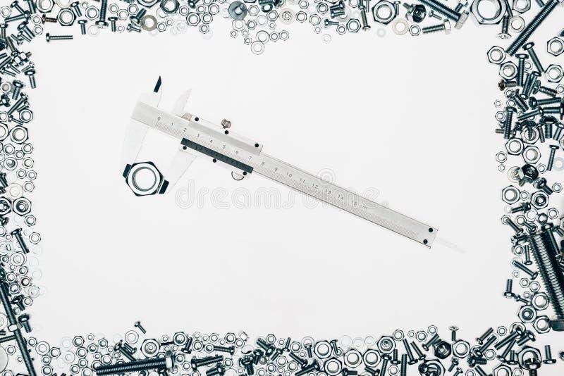 vista superior de los diversos detalles dispuestos de la ingeniería del metal con el calibrador a vernier en centro fotografía de archivo