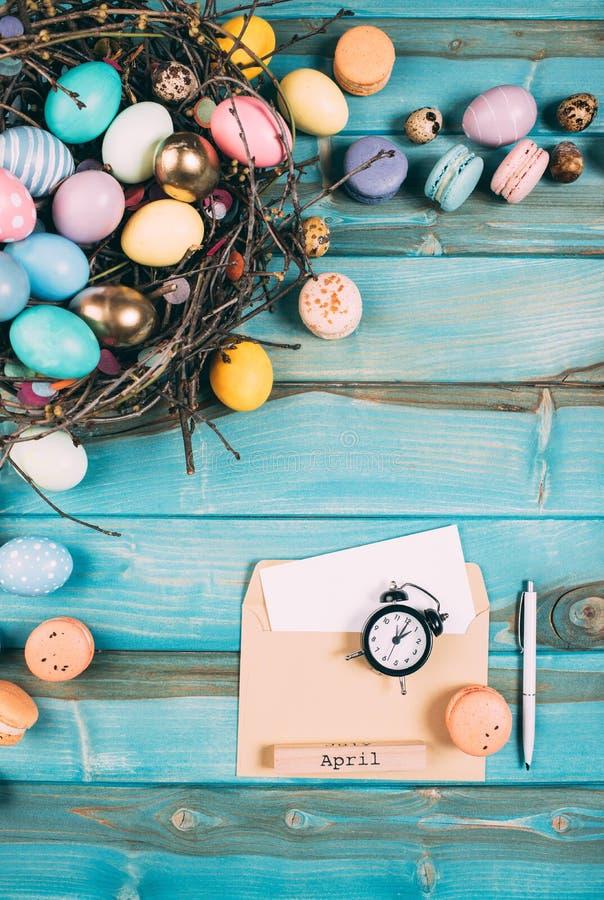 vista superior de los diversos huevos de Pascua en jerarquía y sobre con el despertador en azul imágenes de archivo libres de regalías
