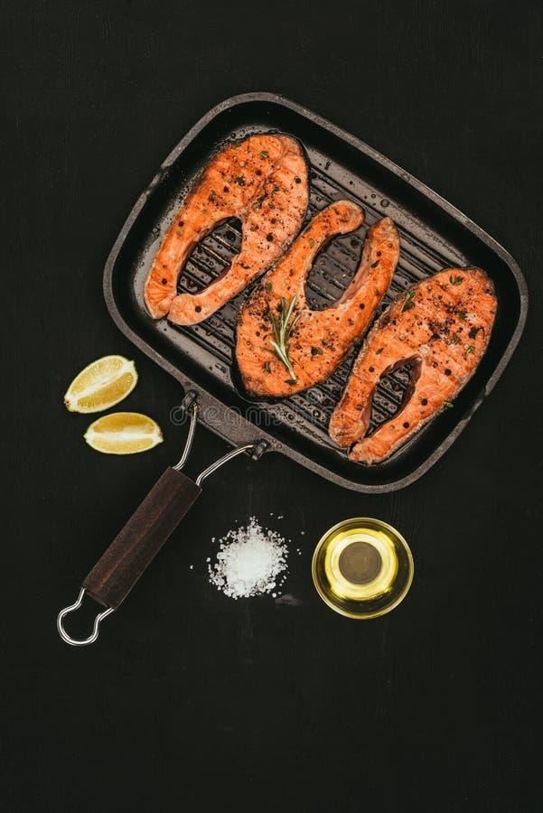 vista superior de los filetes de color salmón en parrilla, la sal, el aceite de oliva y las rebanadas de la cal fotos de archivo libres de regalías