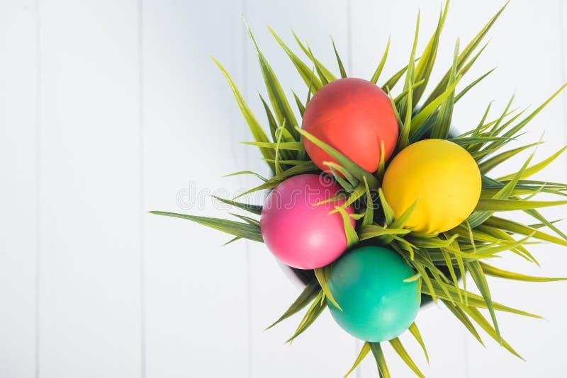 Vista superior de los huevos de Pascua limpios en hierba en el fondo de madera blanco imagenes de archivo