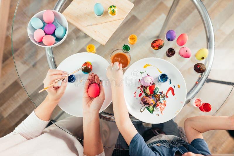 Vista superior de los huevos de pintura caucásicos de la mujer y del niño, preparándose para Pascua imagenes de archivo