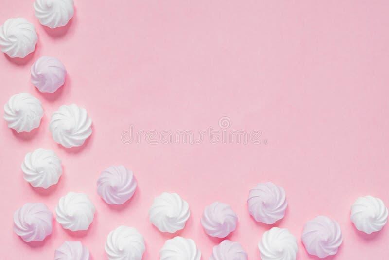 Vista superior de los merengues torcidos blancos y rosados en fondo rosado Postre francés preparado de azotado con el azúcar y el foto de archivo libre de regalías
